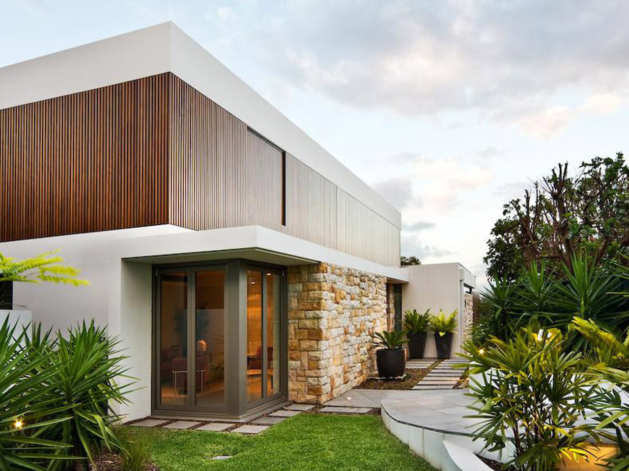 minimalist style home with wood glass stone exterior design